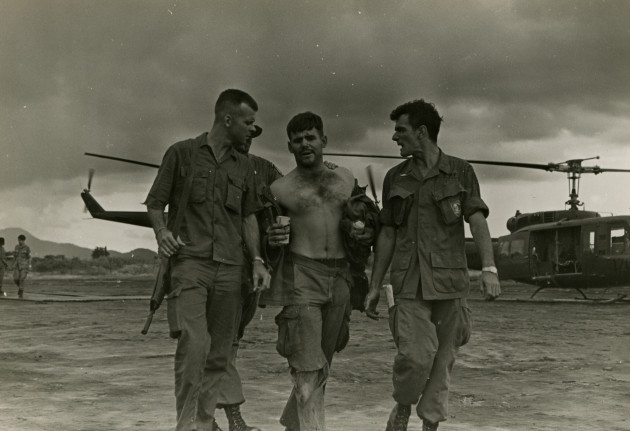 Operation Tailwind Green Beret medic Gary Mike Rose, center, leaves the helipad at CCC Kontum with a cold can of beer, escorted by SSG Bill Sturgeon on the left, and Charles Thomas on the right. Rose was wounded twice on the first day, but, as the only Special Forces medic on the mission was busy attended to the wounded throughout the four day mission, a mission where 49 men, including Rose, were wounded during the top secret mission into Laos. (Photo courtesy of Gene McCarley)