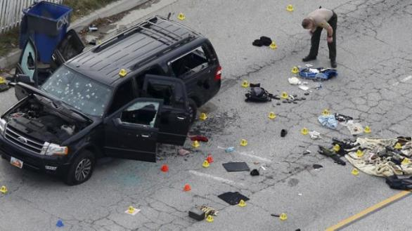 A law enforcement officer looks over the evidence near the remains of a SUV involved in the Wednesdays attack is shown in San Bernardino, California