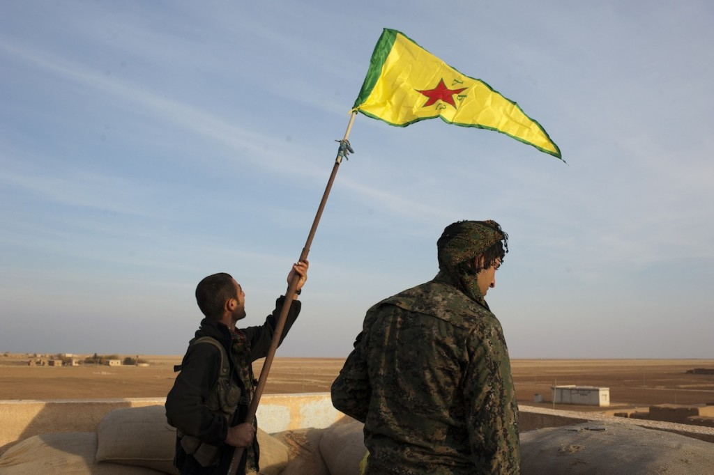 Two Kurdish fighters raise the flag of YPG on the roof of a building formerly occupied by ISIS, now under the control of YPG and YPJ near the frontline of Rabia, in Rojava, Syria, November 19, 2014.