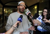 FILE - In this April 18, 2011 file photo of Man Haron Monis, believed to be the gunman inside the Lindt Cafe in Martin Place, speaks to the media as he leaves the Downing Centre in Sydney after a pre-trial hearing where he is accused of sending offending letters to the families of soldiers killed in Afghanistan. Police decided to storm the Lindt Cafe early Tuesday Dec. 16, 2014 when they heard a number of gunshots from inside, and ended with a barrage of gunfire that left two hostages and the gunman dead, and four others wounded. (AP Photo/AAP Image, Dean Lewins) AUSTRALIA OUT, NEW ZEALAND OUT, NO ARCHIVE, NO SALES