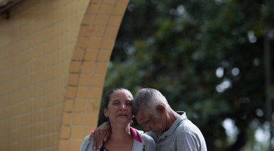 Rosilene Alves Ferreira and her husband mourn the death of their 13-year-old daughter Maria, who was killed by a stray bullet during a shootout between police and alleged drug traffickers, in Rio de Janeiro, Brazil, Friday, March 31, 2017, A video showing the confrontation between police and suspect drug traffickers was shared widely on social media and led to protests. In the video, two officers are seen carrying automatic rifles. They both shoot suspects on the ground. One of the men appears to be moving when he is shot. Rio de Janeiro police spokesman Ivan Blaz told reporters on Friday that the two officers have been charged with murder. | AP Photo/Leo Correa