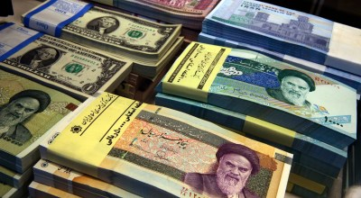 FILE - In this April 4, 2015 file photo, Iranian and U.S. banknotes are on display at a currency exchange shop in downtown Tehran, Iran. Iran's currency is continuing its downward spiral as increased American sanctions loom, hitting a new low on the thriving black market exchange. The Iranian rial fell to 112,000 to the dollar on Sunday, July 29, 2018, from 98,000 to $1 on Saturday. | AP Photo/Vahid Salemi, File