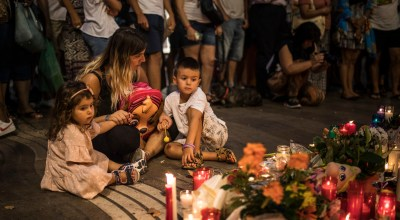 A woman and two children observe a memorial tribute to the victims of the terrorist attack on the historic street of Las Ramblas one day after the terrorist attack, in Barcelona (AP).