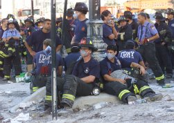 Firefighters rest as rescue efforts continue at the World Trade Center in New York Wednesday Sept. 12, 2001. Many firemen are missing and feared dead in the rubble from the terrorist attack Tuesday. (AP Photo/ Beth Keiser)