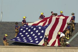 Military and fire personnel get set to unfurl a large American flag on the roof of the Pentagon, Wednesday, Sept. 12, 2001. A hijacked airliner crashed into the structure on Tuesday. (AP Photo/Steve Helber)