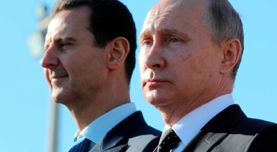 "FILE - This Dec. 11, 2017 file photo, shows Russian President Vladimir Putin, right, and Syrian President Bashar Assad watching troops march at the Hemeimeem air base in Syria. In comments published on the official presidency Telegram channel Wednesday, March 14, 2018, Assad said his country's war on terrorism will continue as long as there is ""a single terrorist"" on Syrian territories. Russia and Iran have been strong backers of Assad, helping him in his bid to regain control of territories. (Mikhail Klimentyev, Sputnik, Kremlin Pool Photo via AP, File)"