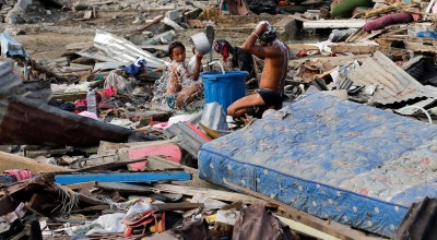 Residents take a bath amidst remains of toppled homes and structures at the earthquake and tsunami-hit Palu, Central Sulawesi, Indonesia on Friday Oct. 5, 2018. As the sun slipped behind the mountains and a gentle breeze blew onshore, hundreds of people gathered on an Indonesian beach Friday to chant a Muslim prayer and remember those they lost one week after a massive earthquake and tsunami ravaged the area, killing more than 1,500 people. (AP Photo/Aaron Favila)