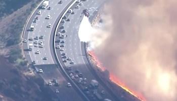 Watch: Firefighting helicopters try to douse flames alongside evacuating cars in California