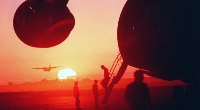 FILE PHOTO: A C-130 Hercules aircraft takes off in the distance as a section of a Military Airlift Command C-5B Galaxy aircraft, foreground, is silhouetted by the morning sun at Grootfontein Logistics Base. The Galaxy is transporting Finnish United Nations troops to Namibia to function as a peacekeeping force. (Photo by USAF)