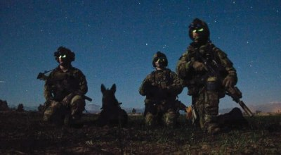 Rangers from Headquarters and Headquarters Company, 3rd Battalion, 75th Ranger Regiment, and a multi-purpose canine pause during a nighttime combat mission in Afghanistan in March 2012. (Photo credit: U.S. Army)