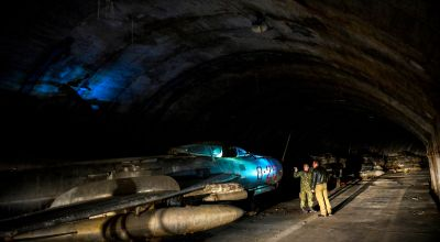 Albanian military personnel walk next to MIG-19 jet fighters inside the main tunnel of the Gjader Air Base built near the city of Lezhe, on February 5, 2019. (GENT SHKULLAKU/AFP/Getty Images)