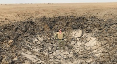 Staff Sgt. Joseph Schmidt, 380th Expeditionary Civil Engineer Squadron explosive ordnance disposal team leader, stands in a crater left by a Mark 84 general-purpose bomb controlled detonation May 18, 2019, on Al Dhafra Air Base, United Arab Emirates. The crater measured approximately 10-feet deep with a circumference of 25 feet. (Photo by Tech. Sgt. Jocelyn Ford)