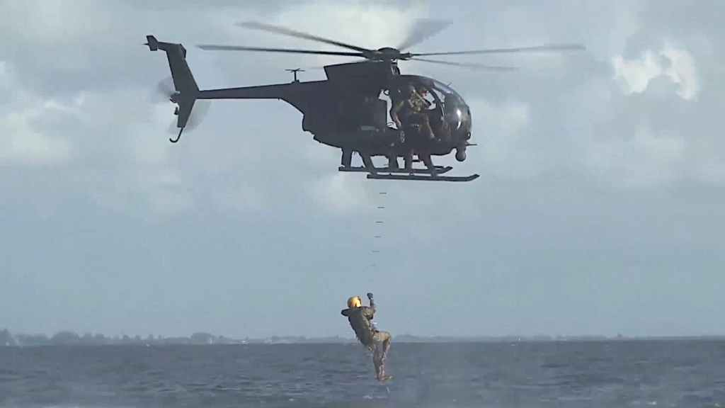 Recovery of a swimmer onto an MH-6 Little Bird helicopter using a caving ladder