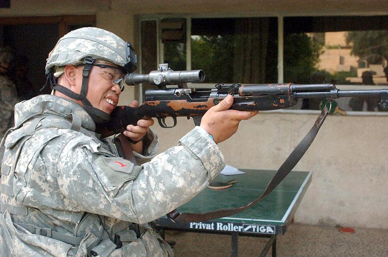 A soldier aims an SKS rifle.