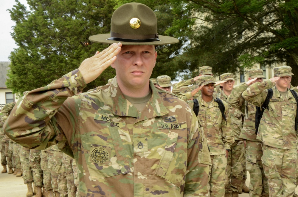 Army Staff Sgt. Joseph D. Moore, an advanced individual training drill sergeant at the U.S. Army Signal School Detachment Student Company on Fort Meade, Md., executes a salute with a formation of soldiers at retreat on May 29, 2018, on Fort Meade. Moore is the first drill sergeant assigned in more than a decade to the detachment, which supports the Defense Information School on Fort Meade. (U.S. Army Photo by Pfc. Lynnwood Thomas)