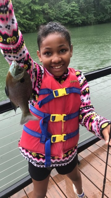 Camper holding up the fish she caught