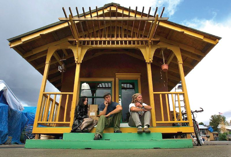 PAMPLIN MEDIA PHOTO: JIM CLARK - Dignity Village founder Jack Tafari (right) sat on the steps of a straw and mud house in 2003 with residents Cat Spry and Lawrence Lyman.