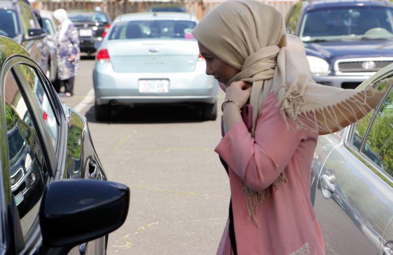 PHOTO COURTESY OF WHITNEY GOMES   - Using a reflection in a car window, Maryam Khatami adjusts her hijab before entering the Imam Madhi Center for Friday prayer. Khatami wears the headscarf at mosque and during prayer.