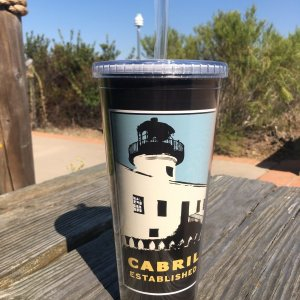 Tall plastic cup with lighthouse on front against blue blackground