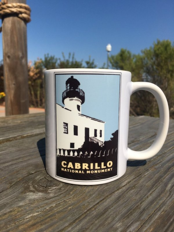 White ceramic mug with lighthouse logo on a light blue background sits on a wall.