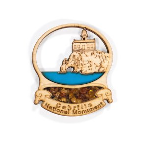 A wood magnet with the Old Point Loma Lighthouse inset with a blue ocean. There is amber below the lighthouse.