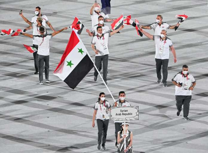 Hind Zaza carrying the Syrian flag with Ahmed Saber Hamsho during the opening ceremony of the Tokyo Olympics 2020