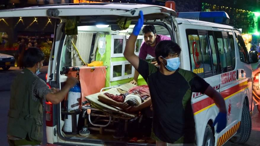 طاقم طبي ينقل رجلاً مصابًا إلى مستشفى في سيارة إسعاف بعد انفجارين قويين خارج مطار كابول في 26 أغسطس 2021