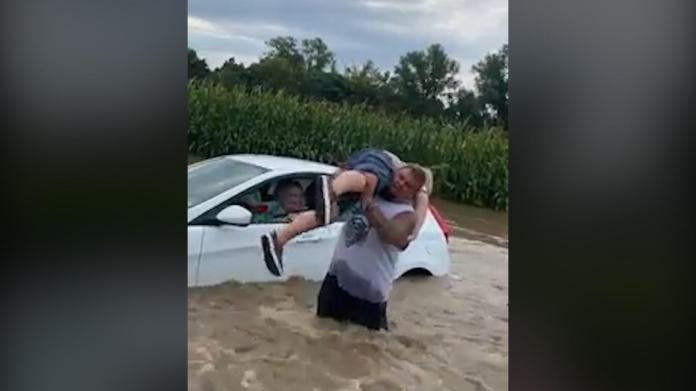 A good Samaritan pulls people out of a flooded car