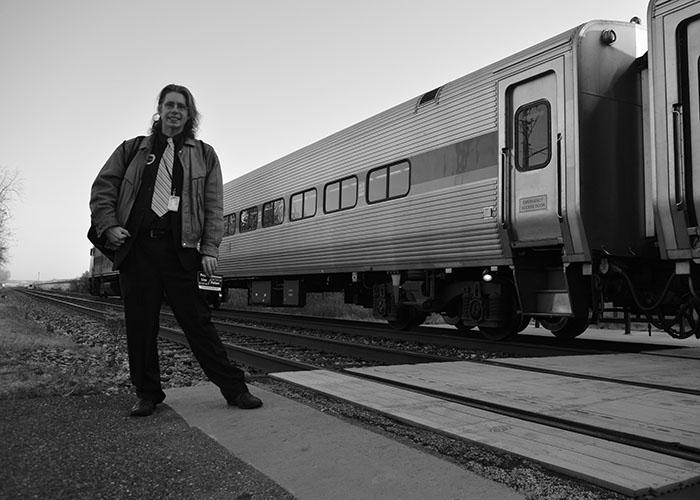 Gregory Sanders is a long time public transit advocate and the vice president of the Purple Line Now coalition. Here, he stands in front of a MARC train at the College Park Metro station, which he takes every day from his home in Ellicott City. His father, Harry Sanders, first proposed the Purple Line. (2015 Capital News Service photo by Brittany Britto)