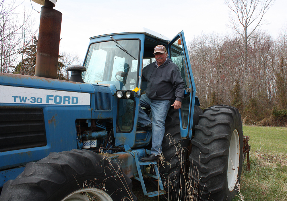Wilbur Levengood, a Caroline County Commissioner, stands on one of his tractors on his land nears Goldsboro, Md. (Photo by J.F. Meils/Capital News Service)