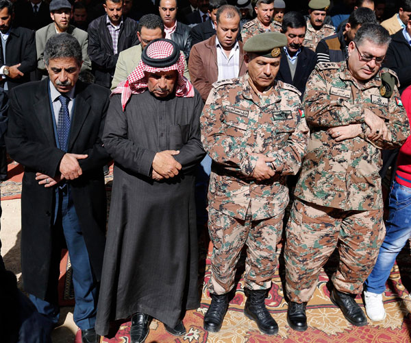 Saif al-Kasasbeh, second from left, father of First Lt. Muath al-Kasasbeh, a murdered Jordanian pilot, prays in Jordan Feb. 4 with other mourners during an event commemorating the pilot's death at the hands of Islamic State militants. (CNS/EPA)