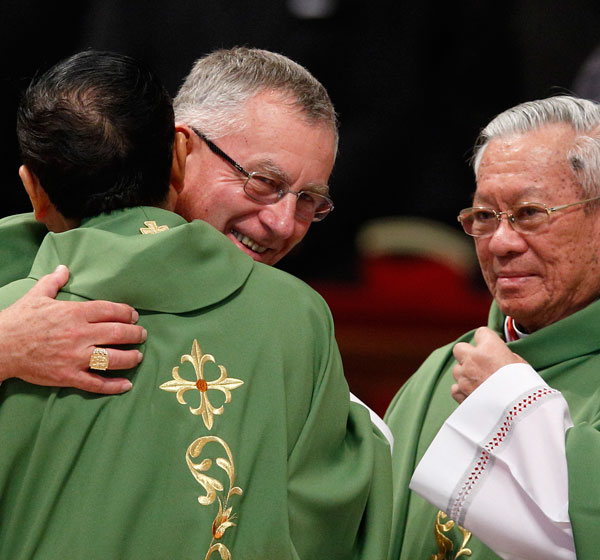 New Cardinals John Dew of Wellington, New Zealand, and Charles Bo of Yangon, Myanmar, exchange the sign of peace during a Mass in St. Peter's Basilica Feb. 15. At right is new Cardinal Pierre Nguyen Van Nhon of Hanoi, Vietnam. (CNS/Paul Haring)