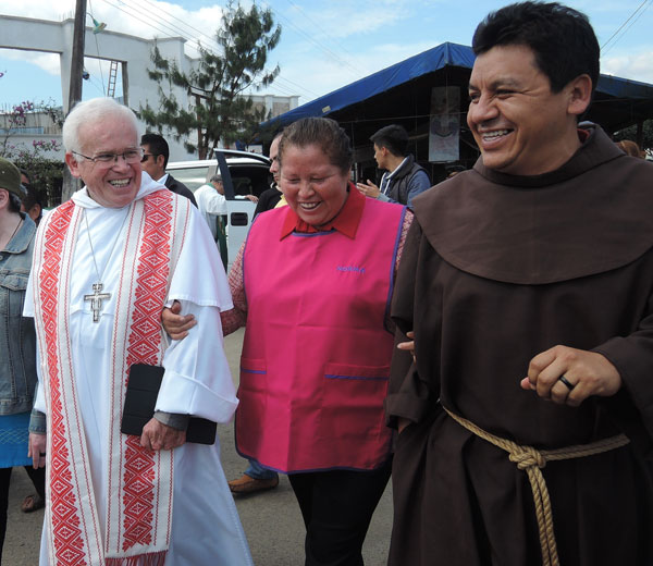 Bishop Raul Vera Lopez of Saltillo, Mexico, Norma Romero Vasquez and Franciscan Brother Tomas Gonzalez Castillo lead a Feb. 14 march through the hamlet of La Patrona, Mexico. Romero and a group of women in the hamlet have fed migrants passing through for the past 20 years, despite having scant resources. (CNS/David Agren)