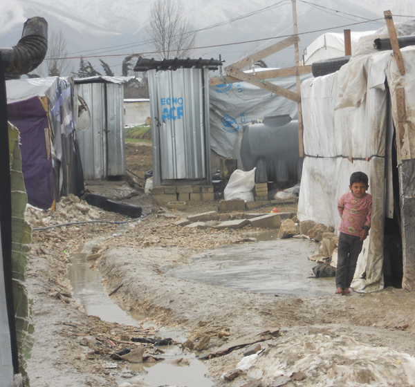 A Syrian child stands barefoot outside a tent Feb. 17 at a camp in Lebanon's Bekaa Valley. This winter's heavy rains have caused the paths between the tents at the settlements to fill with water. (CNS/Brooke Anderson)