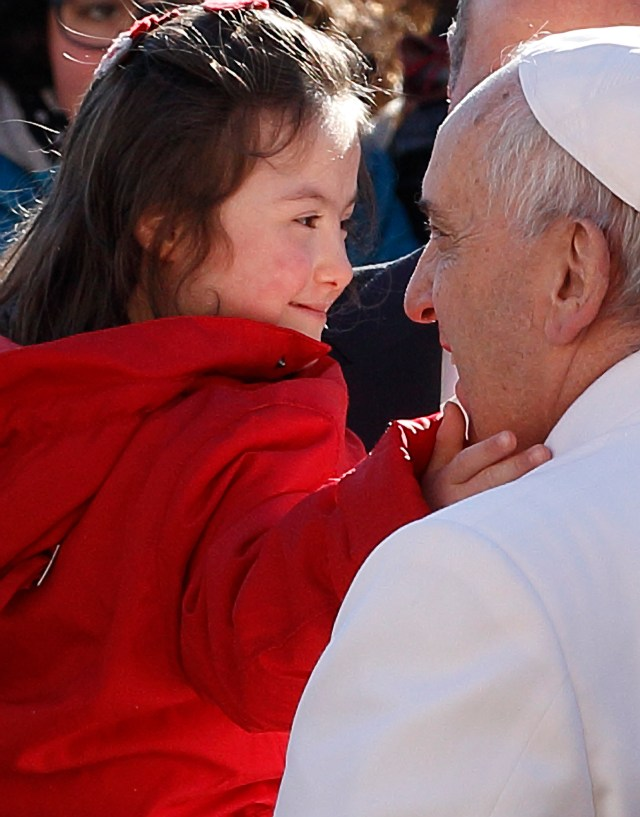 A young girl touches Pope Francis' face during his general audience in St. Peter's Square at the Vatican Feb. 11. (CNS photo/Paul Haring)