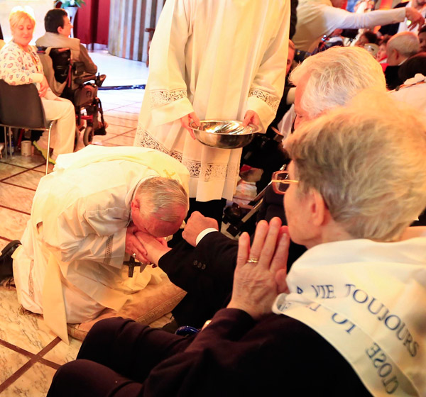 Pope Francis kisses the foot of a disabled person at Our Lady of Providence Center during Holy Thursday Mass and washing of feet in Rome last year. (CNS/Reuters)