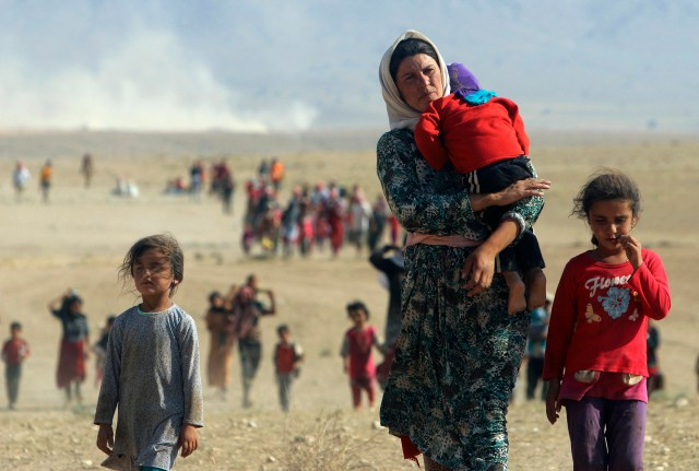 Displaced people fleeing violence in Iraq walk toward the Syrian border town of Elierbeh last summer.  (CNS/Reuters)