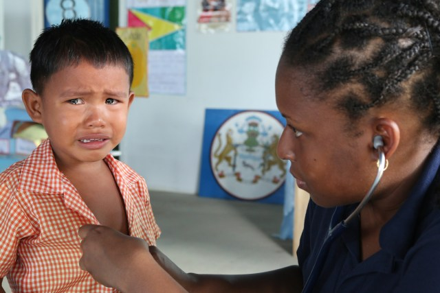 A boy cries as Zwena McLeod of Trinadad, a resident at Johns Hopkins Hospital in Baltimore, examines him at a primary school in Akawini, Guyana. An assistant professor of pediatric emergency medicine at Hopkins who also is a Sister of Mercy has been traveling here every year since 2003 to lead a team of pediatric residents in a two-week course in tropical medicine. (CNS/Bob Roller)