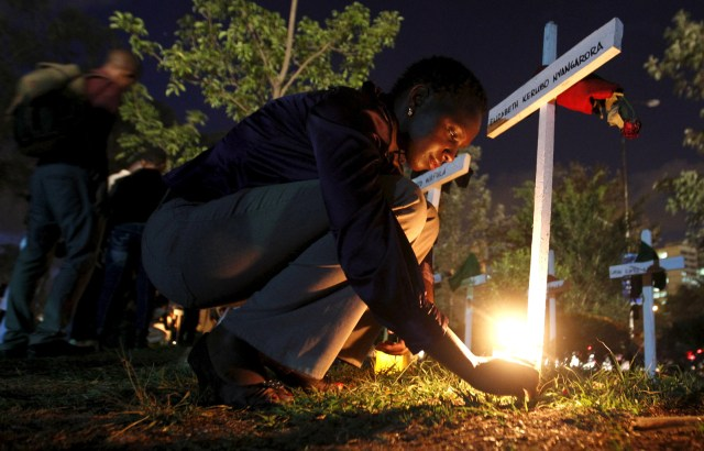 """A woman lights a candle on a wooden cross after an April 14 memorial concert in Nairobi, Kenya, for the 147 people killed in an attack on Garissa University College. Pope Francis is calling for perpetrators of extremist violence in Kenya """"to come to their senses and seek mercy."""" (CNS/Thomas Mukoya, Reuters)"""
