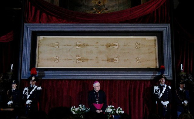 Archbishop Cesare Nosiglia of Turin, papal custodian of the Shroud of Turin, stands in front of the shroud during a preview for journalists in the Cathedral of St. John the Baptist in Turin, Italy, April 18. A public exposition of the shroud, believed by many to be the burial cloth of Jesus, runs from April 19 through June 24, 2015. (CNS photo/Paul Haring)