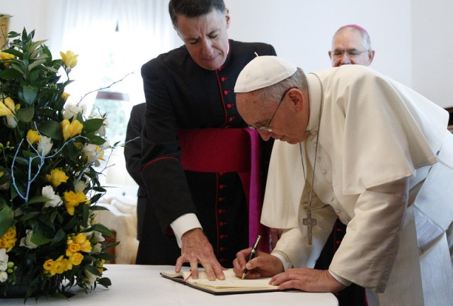 "Pope Francis signs a guest book as he arrives to celebrate Mass at the Pontifical North American College in Rome May 2. Also pictured is Msgr. James F. Checchio, rector of the college. It was the first papal visit to the U.S. seminary since 1980. At the end of Mass, Pope Francis said the visit to the seminary was ""a beautiful and meaningful introduction to my apostolic visit to the United States of America."" (CNS photo/Paul Haring) See POPE-NAC and SERRA-NAC May 2, 2015."