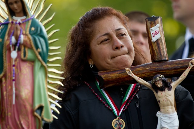 A woman holds a crucifix as people demonstrate against an Arizona immigration law outside the U.S. Supreme Court in 2012. A U.S. bishops' report calls for a complete overhaul of America's immigration detention system. (CNS file/Nancy Wiechec)