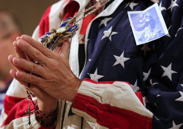 A worshipper holding a rosary and crucifix prays during a Mass celebrated at the Basilica of the National Shrine of the Immaculate Conception in Washington last July 4, the final day of the U.S. bishops' Fortnight for Freedom campaign for 2014. (CNS/Bob Roller)