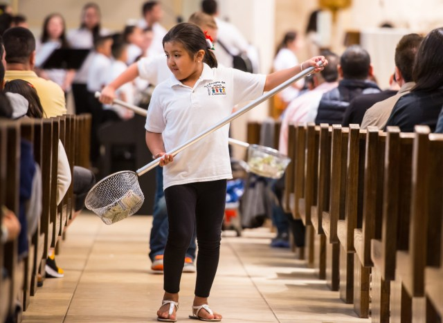 Yelixa Hernandez helps collect donations during Mass at St. Willebrord Church in Green Bay, Wisconsin. (CNS/Sam Lucero, The Compass)