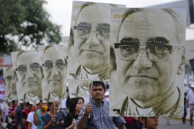 People carry large portraits of Archbishop Oscar Romero during a rally in late March in San Salvador to pay tribute to the archbishop, who was assassinated 35 years ago. (CNS/EPA)