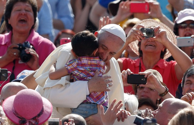 Pope Francis hugs a child as he arrives at the general audience in St. Peter's Square at the Vatican May 13. (CNS/Paul Haring)