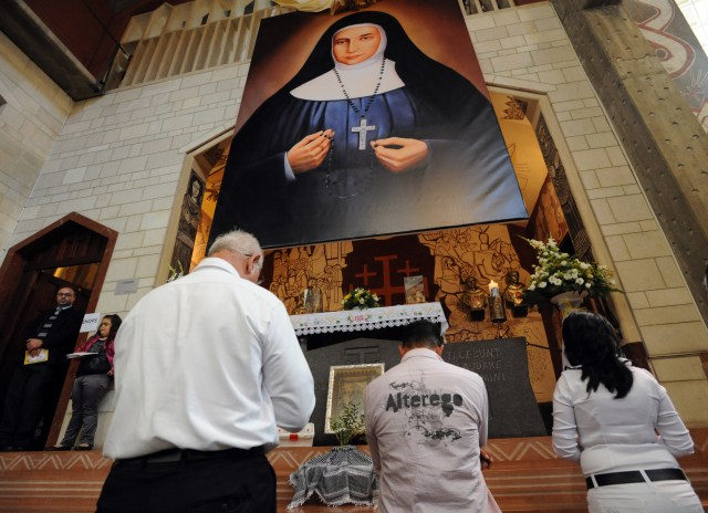 Christian Arabs pray under a large portrait of Mother Marie-Alphonsine  Ghattas during her 2009 beatification Mass in the Church of the Annunciation in Nazareth, Israel, Nov. 22.  She and another Palestinian will be canonized in Rome May 17. (CNS photo/Debbie Hill)