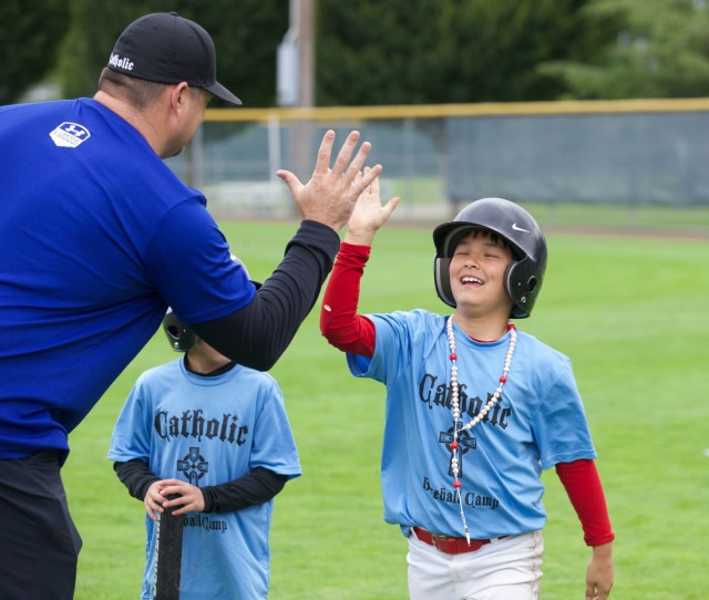 A coach congratulates a player during a Catholic baseball camp in 2014 at Russell Sports Complex in Kent, Wash. (CNS photo/Stephen Brashear)