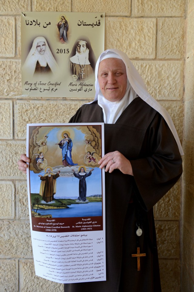 Carmelite Sister Ferial of the Infant Jesus holds a poster April 28 and stands in front of images of Blesseds Mary of Jesus Crucified and Marie-Alphonsine at the Carmel of the Child Jesus Convent in Bethlehem, West Bank. (CNS photo/Debbie Hill)