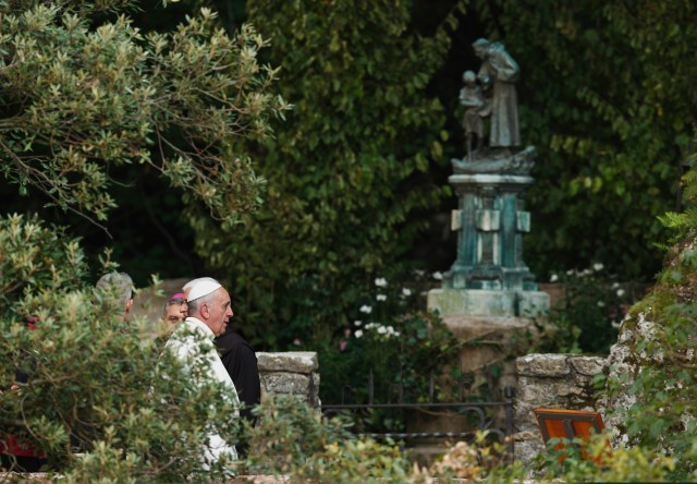 Pope Francis walks near a statue of St. Francis as he visits the hermitage and cell of St. Francis in Assisi, Italy, in 2013. St. Francis spent time in prayer at the hermitage in the countryside outside Assisi. (CNS/Paul Haring)